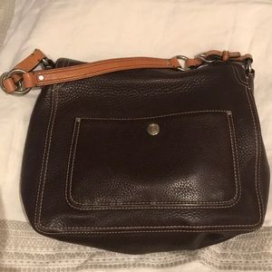 Coach shoulder bag . The clasp sits on top .
